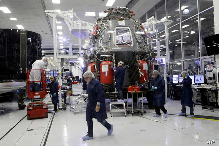 SpaceX employees work on the Crew Dragon spacecraft that will astronauts to and from the International Space Station, from…