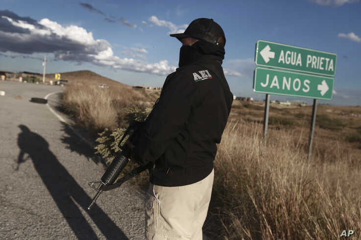 Chihuahua state police officers man a checkpoint in Janos, Chihuahua state, northern Mexico, Tuesday, Nov. 5, 2019. Drug cartel