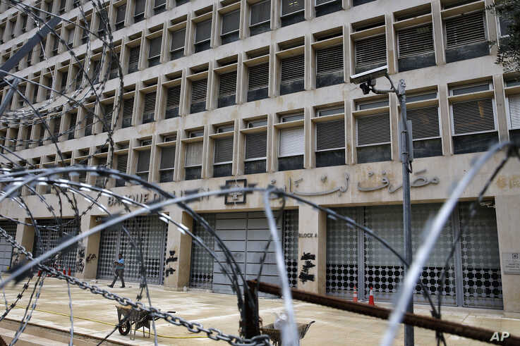 In this Wednesday, March 18, 2020 photo, a worker walks outside the Lebanese Central Bank that has been shut down as part of…