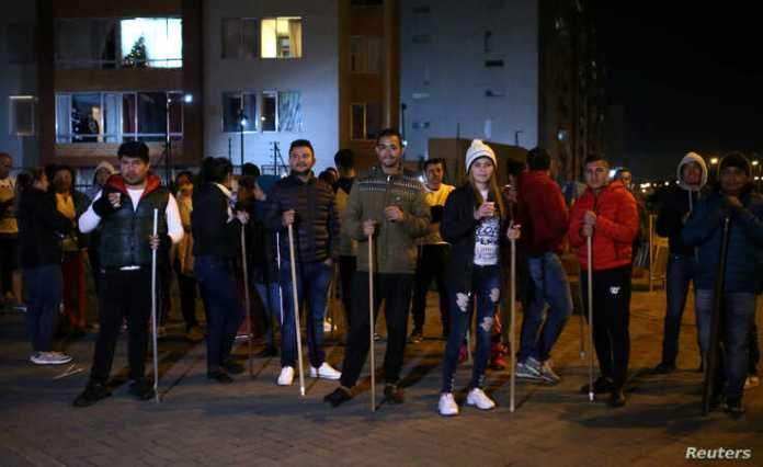 Residents hold sticks as they stand in front of their apartment block to guard their homes from possible looting after a curfew