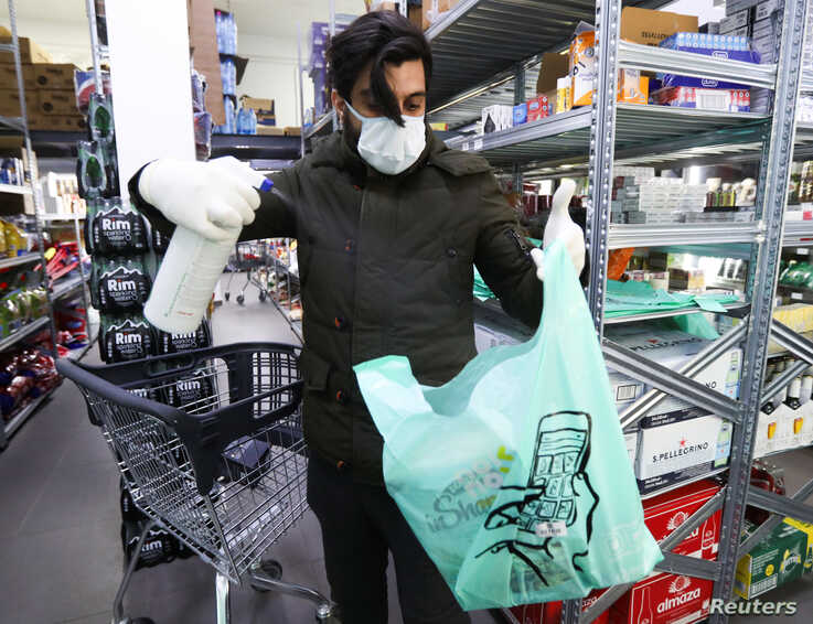 A worker sanitizes a plastic bag of groceries before being delivered to the customer, amid the coronavirus disease (COVID-19)…