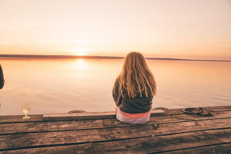 Leya på bryggan, spanar in solnedgången på Visingsö
