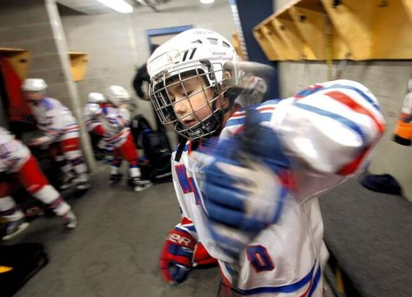 Nine-year-old Daimon Gardner prepares to hit the ice with his teammates before his game in Warrod, Minnesota, earlier this week . He plays on the Warrod squirt a team.