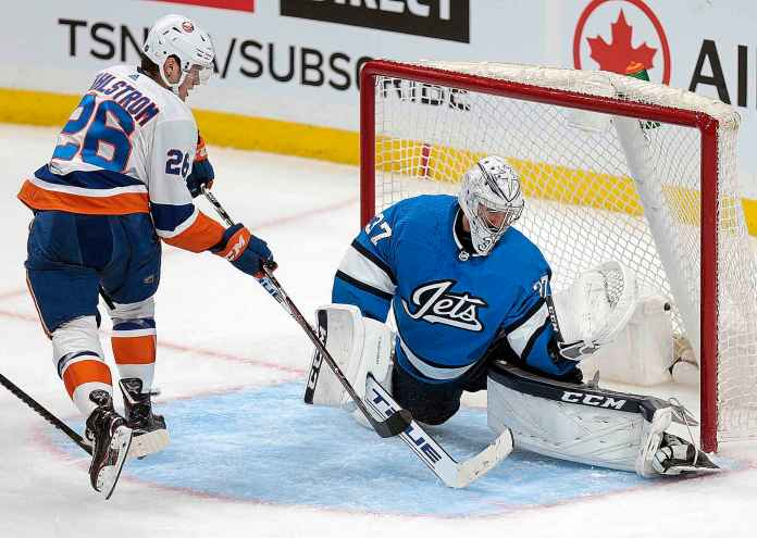 Winnipeg Jet's net-less Connor Hellebuyck foils Oliver Wahlstrom of New York Islanders in the second Thursday period.