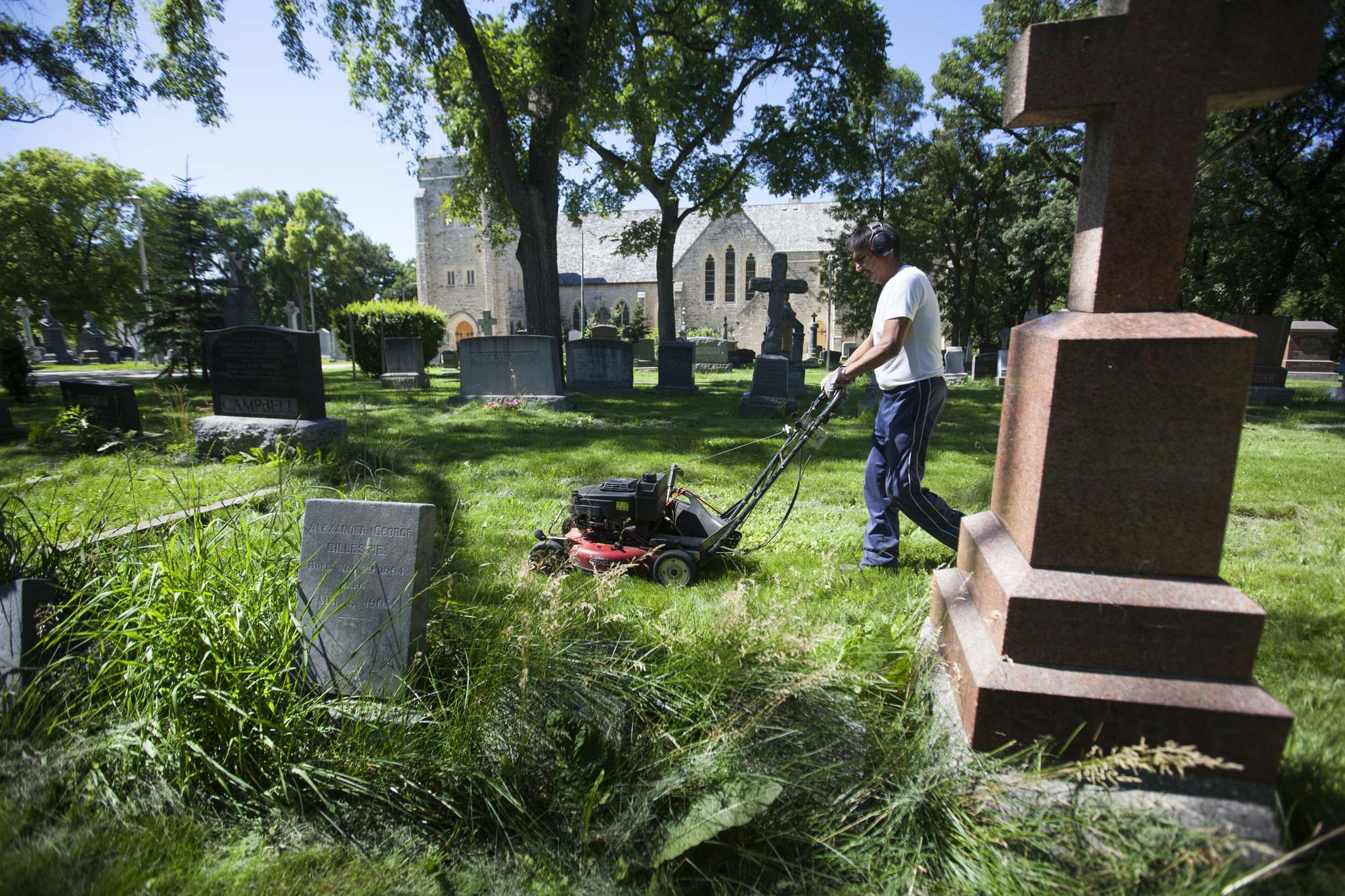 RUTH BONNEVILLE / WINNIPEG FREE PRESS</p><p>Groundskeeper Dennis Beaulieu works his way around the headstones and uneven ground to mow the lawn at the historic cemetery near St. John's Anglican Cathedral in Winnipeg.</p>