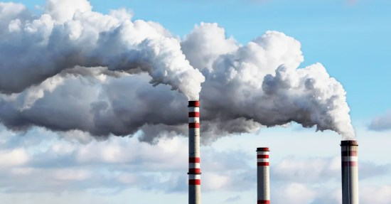 three red and white smoke stacks, two of which are spewing white clouds of smoke