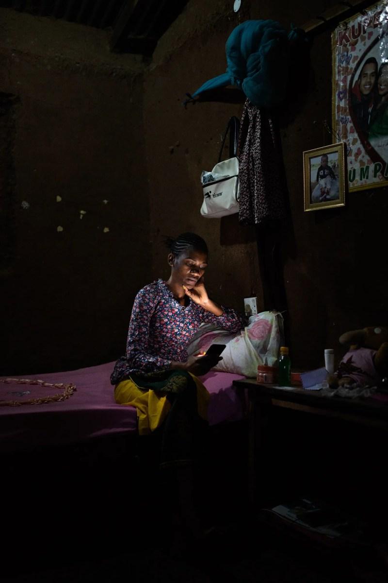 donna seduta sul letto guardando smartphone