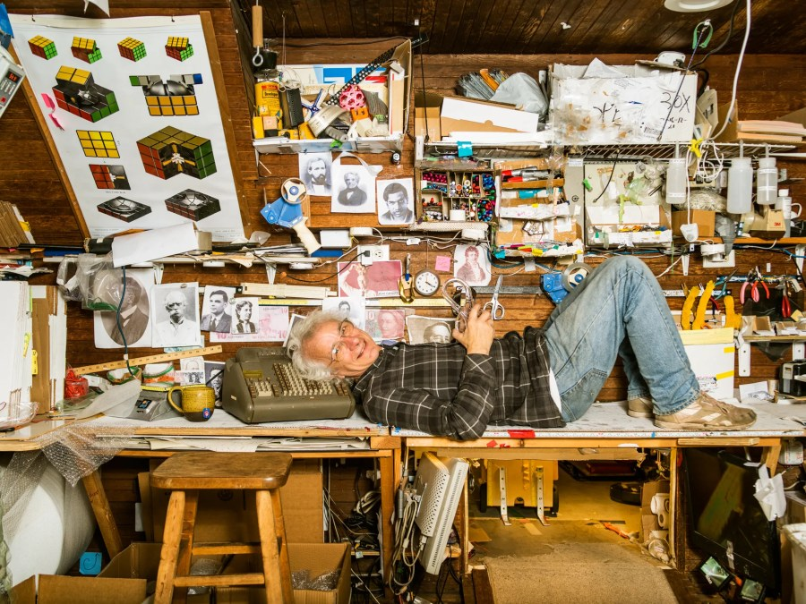 Cliff Stoll in a cluttered workshop lying on a desk