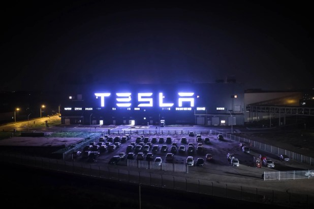 Cars: Tesla illuminated on the side of the new Shanghai factory at night