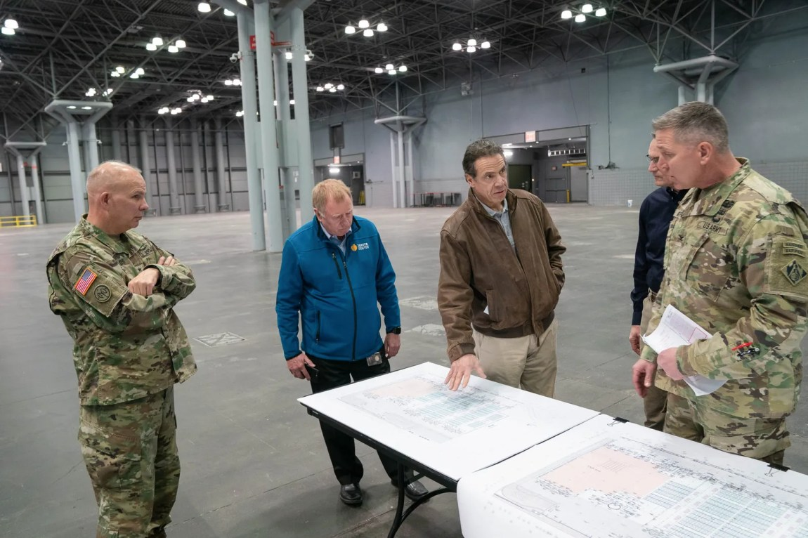 Men look at a plan on a table in a convention center