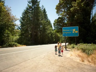 a family standing next to a welcome to California sign
