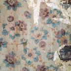Fyra tapetlager och tidning under masoniten i Selmas kammare. Underst syns stockväggen in till gamla farstun.