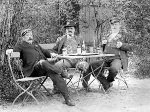 Välmående herrar i en trädgård i Falsterbo.