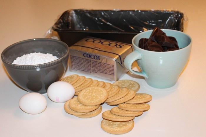Du behöver kokosfett, choklad, florsocker, ägg och kex. Klä en brödform med plastfolie.