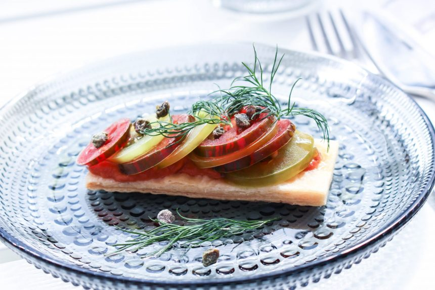 Mördegsplatta med tomat och sardellkräm toppad med färska skivade tomater och friterad kapris.