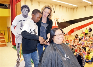Student Kiani Chabakuli (left), with assistance from Sherri Paquette of Flipped Out Hair and Makeup Boutique, chops off the hair of teacher Liz Villegas. Two ponytails will be donated to make wigs.
