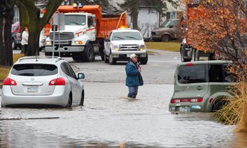 A man walks across a flooded portion of Grand River Avenue in Brantford after the Grand River flooded parts of the town in February 2018. The Grand River Conservation Authority was notified Friday that its flood management funds from the province were being reduced by 48 per cent.  John Rennison The Hamilton Spectator