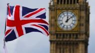 Eine britische Nationalflagge, der Union Jack, weht vor dem Uhrturm Big Ben.