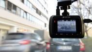 Eine sogenannte Dash-Cam, befestigt an der Windschutzschreibe, filmt den Verkehr aus einem Auto.