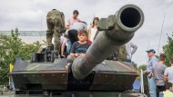 Ein Junge sitzt beim Tag der offenen Tür der Bundesregierung im August 2019 auf einem Leopard 2 Panzer.