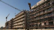 Baukräne stehen an einer Baustelle in Berlin.