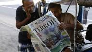 Männer in Colombo lesen am Tag nach den Anschlägen in einer Zeitung.