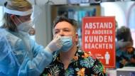 Die Mitarbeiterin eines Friseurstudios macht einen Antigen-Schnelltest auf das Coronavirus.