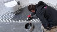 Ein Handwerker arbeitet an einem Messestand an Fliesen für ein Bad.