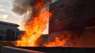 Brand am Uni-Campus Bockenheim: Die Flammen schlagen mehr als zehn Meter hoch als die Feuerwehr eintrifft.