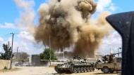 Südlich von Tripolis steigt nach einem Luftschlag hinter einem Panzer der Streitkräfte der libyschen Übergangsregierung eine Rauchsäule auf.