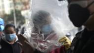 In Wuhan wagt sich niemand ohne Maske in die Öffentlichkeit, und manche Chinesen ziehen sich außerdem Plastiktüten und Gummihandschuhe über.