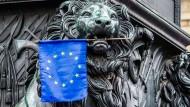 Eine EU-Flagge im Maul einer Löwen-Statue in München.