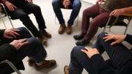 Mitglieder einer Gruppe für trockene Alkoholiker sitzen in einer baden-württembergischen Stadt zum Therapiegespräch in einer Stuhlrunde zusammen.