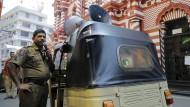 Ein sri-lankischer Polizist verkündet am Mittwoch vor einer Moschee in Colombo Sicherheitshinweise.