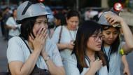 Diese Frauen mussten ihr Büro verlassen. Die Helme sollen sie vor Trümmern schützen.