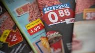 Prospekte verschiedener Lebensmittelhändler liegen auf einem Tisch.