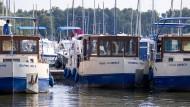 Ein Urlauber steuert beim Einführungskurs ein Hausboot des Vermieters Kuhnle-Tours an einen der Stege im Müritz-Hafen.