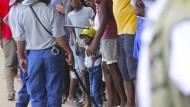 Menschen stehen Schlange vor einem Supermarkt in Zimbabwes Hauptstadt Harare.