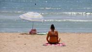 Eine Frau sonnt sich am Strand von Can Pastilla in Palma de Mallorca.