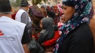 Im libyschen Lager Sintan warten Menschen auf die Ausgabe von Essen.