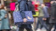 Ein Mann eilt mit einem verpackten Geschenk zwischen den anderen Passanten die Einkaufsmeile Zeil in Frankfurt entlang.