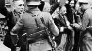 Im Warschauer Getto: Wehrmachtsangehörige kontrollieren jüdische Einwohner.