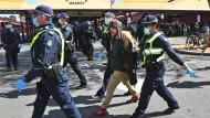 Polizisten führen Anti-Corona-Demonstranten in Melbourne ab.