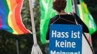 """Eine Aktivistin trägt ein Plakat mit der Aufschrift """"Hass ist keine Meinung"""", um gegen Hassnachrichten im Internet zu protestieren."""