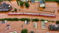 Ein Regionalzug steht im Bahnhof des Ortes Kordel in Rheinland-Pfalz, umspült vom Hochwasser der Kyll. Als der Strom ausfiel, blieb auch die Bahn am Mittwoch liegen.