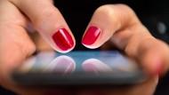 Eine Frau tippt auf einem Smartphone (Symbolbild).