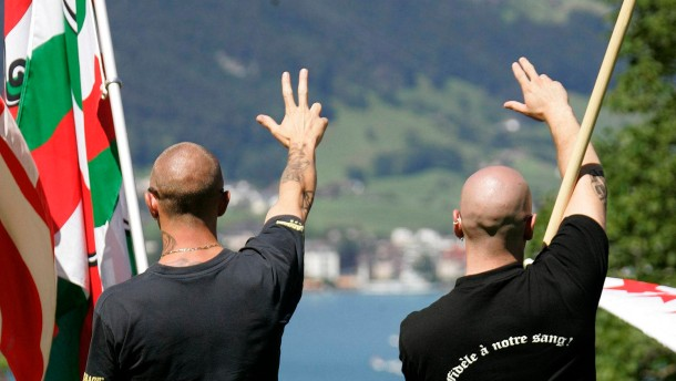 Right-wing extremists give fascist salutes during a Swiss national holiday celebration on the Ruetli
