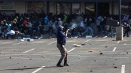 Einsatz gegen Plünderer: Ein Polizist schießt in Soweto Gummigeschosse in die Menge.