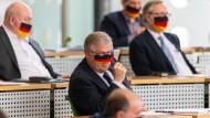 Abgeordnete der sächsischen AfD im April mit Deutschland-Masken im Landtag