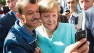Kanzlerin Merkel mit einem Flüchtling aus dem Irak im September 2015.